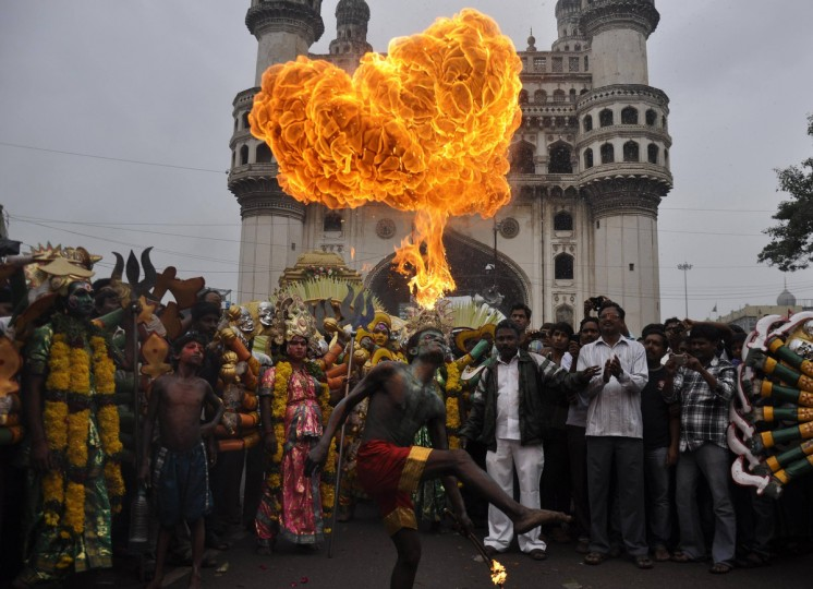 """A performer blows fire from his mouth as he performs in front of the historical monument Charminar during the annual Hindu religious festival of Bonalu in the southern Indian city of Hyderabad. The word """"Bonalu"""" is derived from the Telugu word """"Bhojanalu"""", which refers to the food offered to Goddess Kali, the Hindu goddess of power. The main ritual in the month-long festival consists of offering cooked rice, jaggery, curd, water and other dishes brought by women in earthen pots to Goddess Kali. Devotees believe that the offerings will ward off evil and epidemics during the monsoon period. (Reuters)"""