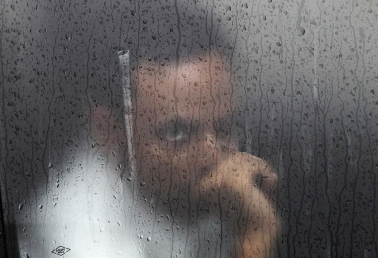 A commuter watches through the window of a car during a rain shower in New Delhi August 6, 2013. Rainfall in August and September, the second half of the four-month long monsoon season, is likely to be normal or 96 percent of the long-term average, the state-run weather department said. (Anindito Mukherjee/Reuters)