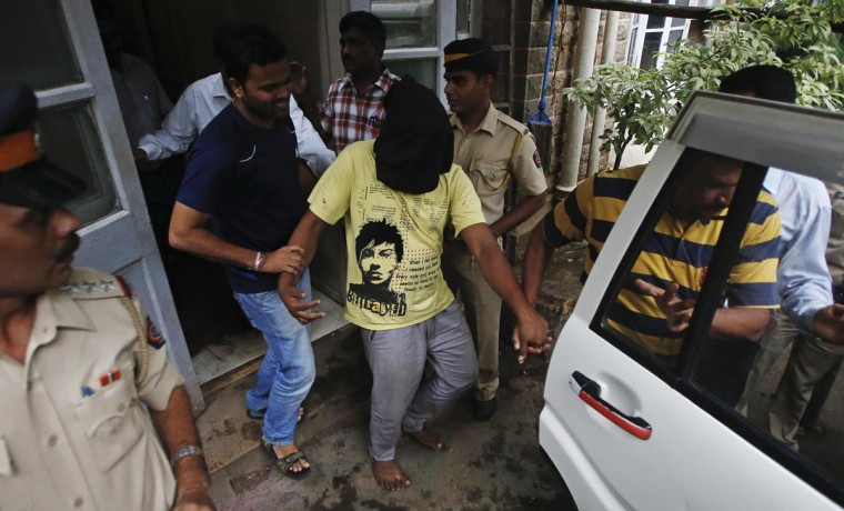Police officers escort a man (face covered), who was arrested in connection with the gang-rape of a photo journalist, at a court in Mumbai August 25, 2013. Indian police arrested the man, the third suspect in connection with the gang-rape, an official said on Saturday. (Danish Siddiqui/Reuters)