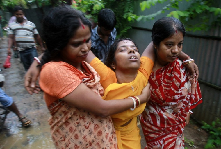 A woman (C) is helped by other women to walk after she fainted on hearing of the death of her husband after a residential house collapsed at Kumarpera village on the outskirt of Agartala, capital of India's northeastern state of Tripura. At least three people died and three were injured after a residential house collapsed on Wednesday, officials said. (Jayanta Dey/Reuters)