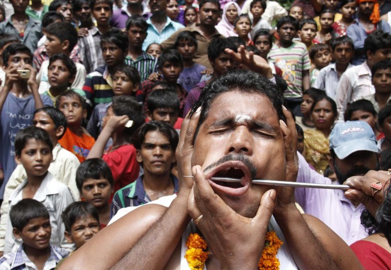"A Hindu devotee gets his cheeks pierced as he takes part in an annual religious procession called ""Shitla Mata"" in the northern Indian city of Chandigarh August 11, 2013. Hindu devotees subject themselves to painful rituals during the religious procession to demonstrate their faith and as a penance to the deity at a temple dedicated to the goddess Shitla. (Ajay Verma/Reuters)"