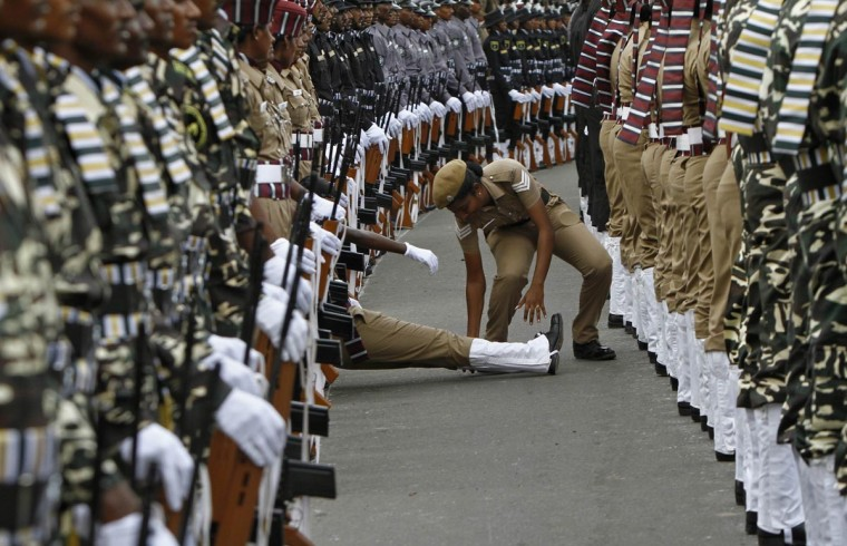 An Indian policewoman helps her comrade who fainted during the full-dress rehearsal for India's Independence Day celebrations in the southern Indian city of Chennai August 13, 2013. India commemorates its Independence Day on August 15. (Babu/Reuters
