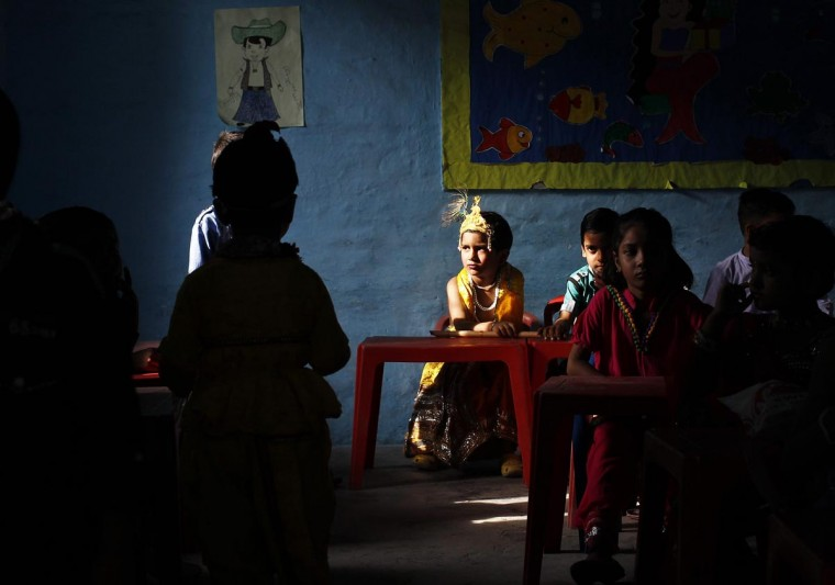 A schoolboy dressed as Hindu Lord Krishna waits for his performance to start inside a classroom during the celebrations to mark Janmashtami festival in New Delhi August 27, 2013. The festival, which marks the birth anniversary of Lord Krishna, will be celebrated across India on Wednesday. (Anindito Mukherjee/Reuters)
