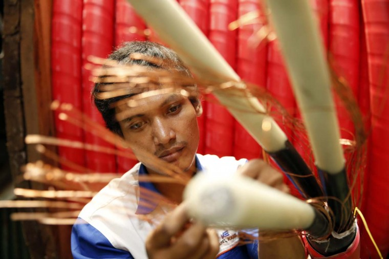 A worker counts copper wires at PT Voksel Electric at Cibubur district on the outskirts of Jakarta. (Beawiharta / Retuers)