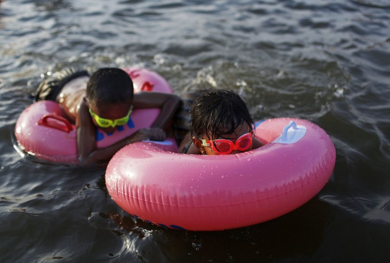 Children swim at Ancol beach during the Eid al-Fitr holiday in Jakarta, August 9, 2013. (Beawiharta/Reuters)