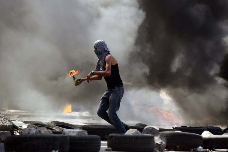 A Palestinian protester gets ready to throw a Molotov cocktail during small clashes with Israeli forces following the funerals of Robin Zayed, Younis Jahjouh and Jihad Aslan at Qalandiya Refugee Camp near the West Bank city of Ramallah August 26, 2013. Israeli troops shot dead the three Palestinians and wounded about a dozen in an early morning raid on Monday to arrest a suspected militant in a refugee camp near Jerusalem, Palestinian medical sources told Reuters. (Darren Whiteside/Reuters)
