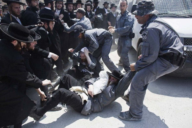 Israeli policemen drag ultra-Orthodox protesters during clashes in the town of Beit Shemesh, near Jerusalem August 12, 2013. An Israeli police spokesperson said some 21 ultra-Orthodox protesters were detained on Monday in the town during clashes with police after a group of them broke into a construction site to prevent work from taking place at the site they believe contains ancient graves. (Nir Elias/Reuters)