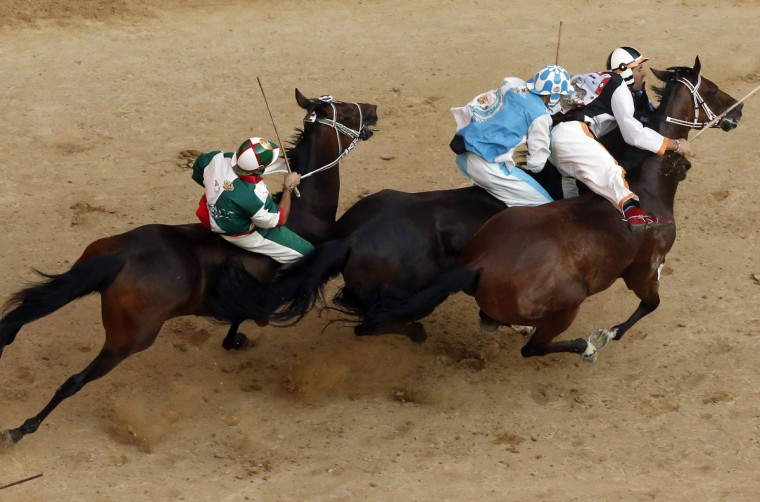 Jockey Jonathan Bartoletti (R) of the Lupa (Wolf) parish leads ahead of Jockey Giovanni Atzeni of the Onda (Wave) parish (C) and Francesco Caria of the Oca (Goose) parish during the Palio of Siena horse race in Siena August 16, 2013. (Stefano Rellandini/Reuters)