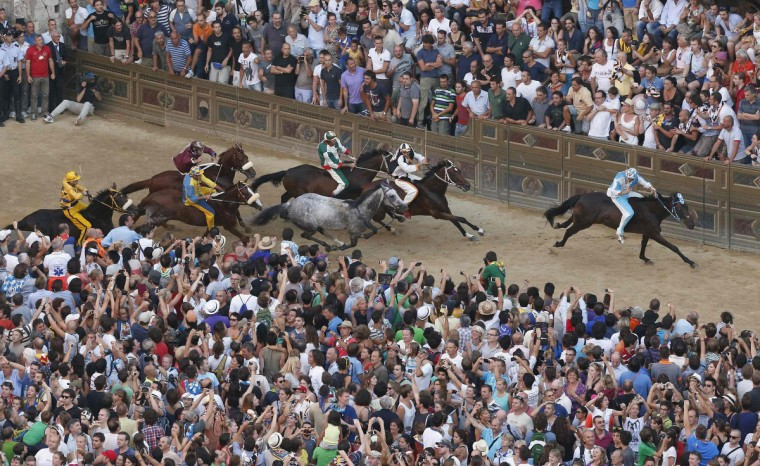Jockey Giovanni Atzeni (R) of the Onda (Wave) parish leads ahead of jockey Jonathan Bartoletti of the Lupa (Wolf) parish during the Palio of Siena horse race in Siena August 16, 2013. (Stefano Rellandini/Reuters)