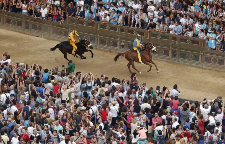 Jockey Sebastiano Murtas (R) of the Tartuca (Turtle) parish leads ahead of Giuseppe Zedde of the Aquila (Eagle) parish, during the fifth of six trial horse races in Del Campo square in Siena August 15, 2013. (Stefano Rellandini/Reuters)