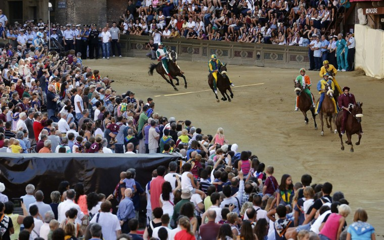 Jockey Alessio Migheli (R) of the Torre (Tower) parish leads the pack during the fourth of six trial horse races in Del Campo square in Siena August 15, 2013. Every year on July 2 and August 16, almost without fail since the mid-1600s, 10 riders compete bareback around Siena's shell-shaped central square in a bid to win the Palio, a silk banner depicting the Madonna and child. (Stefano Rellandini/Reuters)