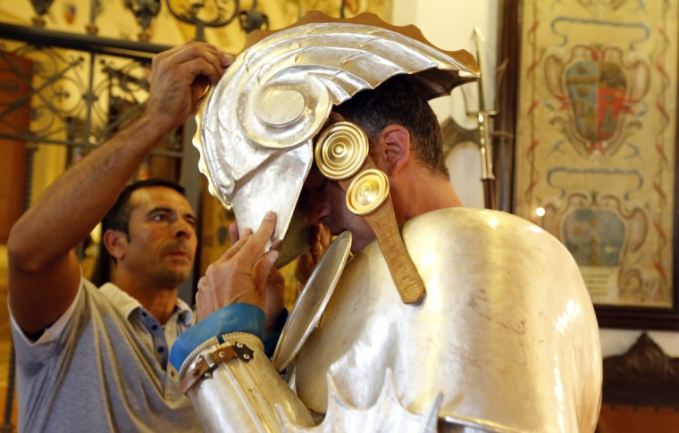 A member of the Onda (Wave) parish prepares for the parade before the Palio horse race in Siena August 16, 2013. (Stefano Rellandini/Reuters)