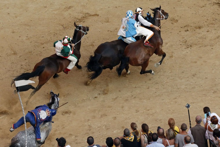 Jockey Jonathan Bartoletti, right, of the Lupa (Wolf) parish leads ahead of Jockey Giovanni Atzeni of the Onda (Wave) parish, Francesco Caria of the Oca (Goose) parish and Luigi Bruschelli of the Nicchio (Shell) parish during the Palio of Siena horse race in Siena August 16, 2013. Every year on July 2 and August 16, almost without fail since the mid-1600s, 10 riders compete bareback around Siena's shell-shaped central square in a bid to win the Palio, a silk banner depicting the Madonna and child. (Stefano Rellandini/Reuters)