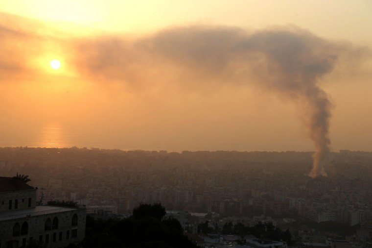 Smoke rises behind buildings from the site of an explosion in Beirut's southern suburbs. Rescue workers in the southern Beirut district hit by an explosion on Thursday have found nine bodies, a witness at the scene said. The powerful blast engulfed several cars in flames and also trapped people in a nearby building. (Mohamed Azakir/Reuters photo)