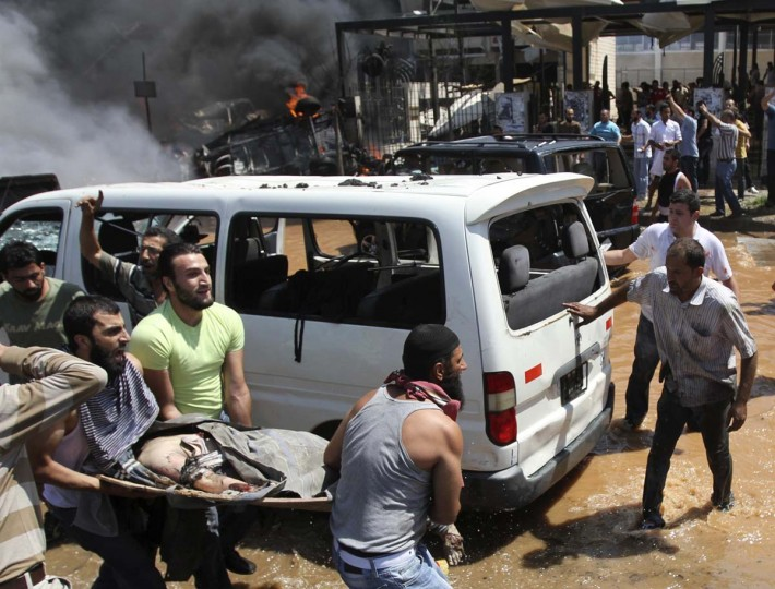 People carry a dead body outside one of two mosques hit by explosions in Lebanon's northern city of Tripoli. At least 13 people were killed and more than 50 wounded in two explosions, security sources and witnesses said. (Omar Ibrahim / Reuters)