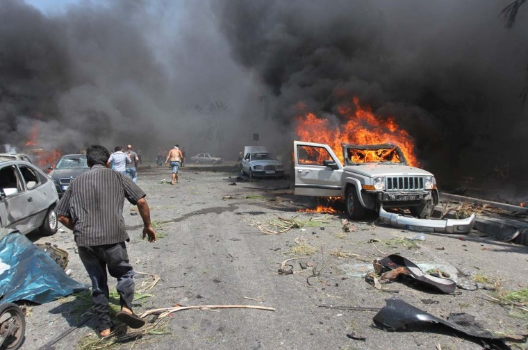 People run for help as a car burns outside one of two mosques hit by explosions in Lebanon's northern city of Tripoli, on Aug. 23, 2013. At least 13 people were killed and more than 50 were wounded in two explosions, security sources and witnesses said. (Omar Ibrahim / Reuters)
