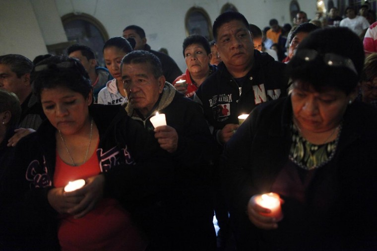 Relatives and neighbors of 12 people abducted in May, hold candles during a mass at San Francisco de Asis church in Tepito neighborhood in Mexico City August 26, 2013. Mexican authorities have identified the remains of 10 out of 12 youths abducted from a Mexico City club in May and dumped in a mass grave, a government official said on Monday, a crime that stoked fears drug gang violence is creeping into the capital. (Edgard Garrido/Reuters)