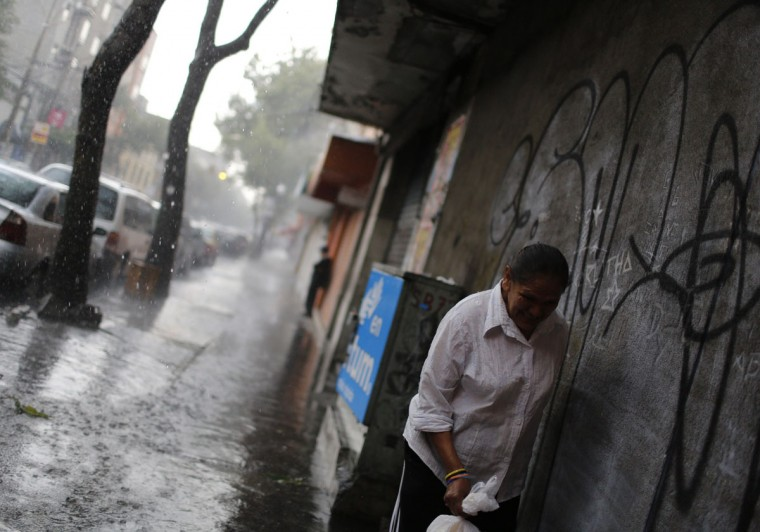 A woman takes shelter from the heavy rain under a balcony at a working class neighborhood in Mexico City, August 8, 2013. (Tomas Bravo/Reuters)