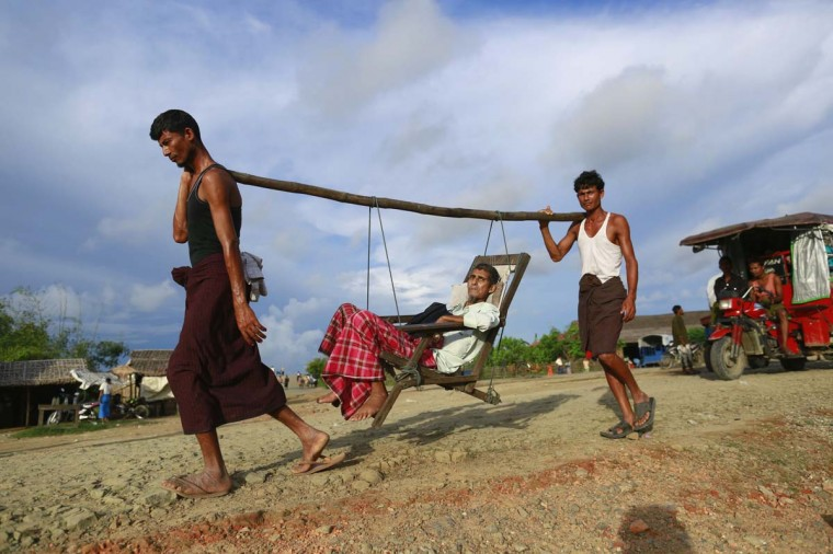 Rohingya men carry a patient to a hospital outside Sittwe August 12, 2013. (Soe Zeya Tub/Reuters)