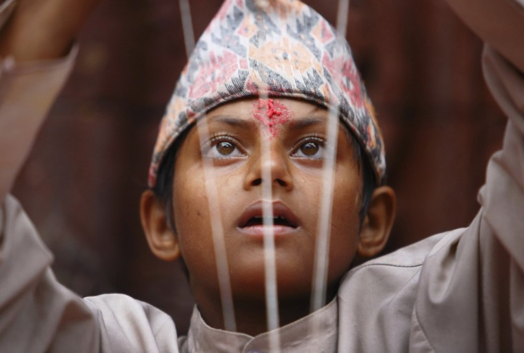 A young Hindu priest arranges sacred thread during the Janai Purnima, or Sacred Thread, Festival at the premises of Pashupatinath temple in Kathmandu. Hindus take holy baths and change their sacred thread, also known as Janai, for protection and purification during the festival. (Navesh Chitrakar/Reuters)
