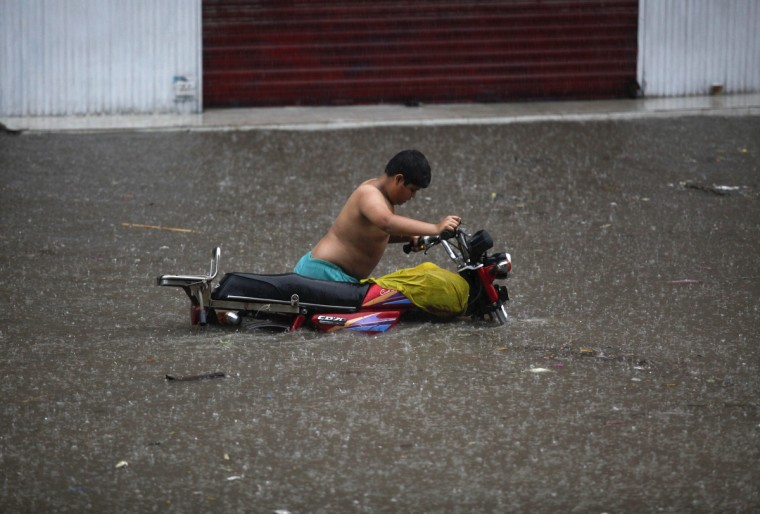 A motorcyclist wades through a flooded street after a heavy downpour in Lahore. (Mohsin Raza/Reuters)