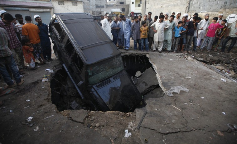 Residents gather at the site of a Wednesday night bomb blast in the Karachi. A bomb killed 11 people in a poor district of Pakistan's financial hub of Karachi on Wednesday, mostly teenagers playing street football at a crowded market, officials said. (Athar Hussain/Reuters)