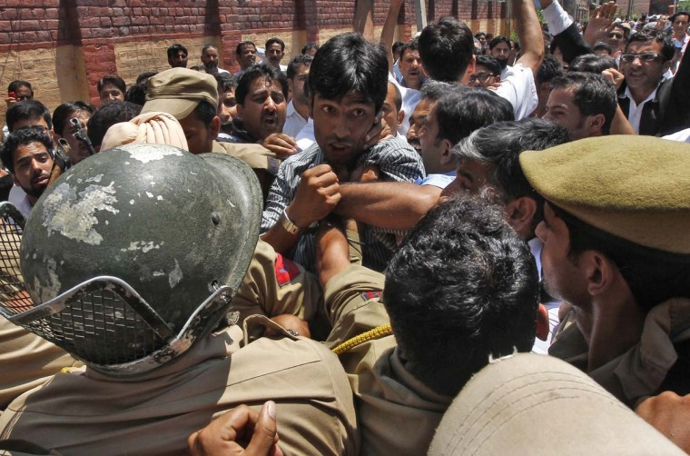 Members of the Jammu and Kashmir High Court Bar Association (JKHCBA) scuffle with Indian policemen during a protest against recent riots in Srinagar August 12, 2013.Three people died in riots between Hindus and Muslims over the weekend. Opposition parties linked the rioting to the renewed border tensions between India and Pakistan, because some of the protesters involved had brandished a Pakistani flag. †Pakistan accused Indian troops of firing shells across the disputed border in Kashmir on Monday and tensions ran high in both countries after last week's killing of Indian soldiers set off a wave of skirmishes between the two nuclear-armed rivals. REUTERS/Danish (Danish Ismali/Resuters)