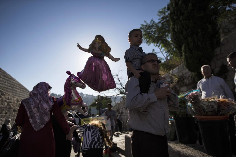 Palestinian children hold balloons as they walk outside Jerusalem's Old City on the first day of Eid al-Fitr, which marks the end of the holy month of Ramadan August 8, 2013. (Ronen Zvulun/Reuters)