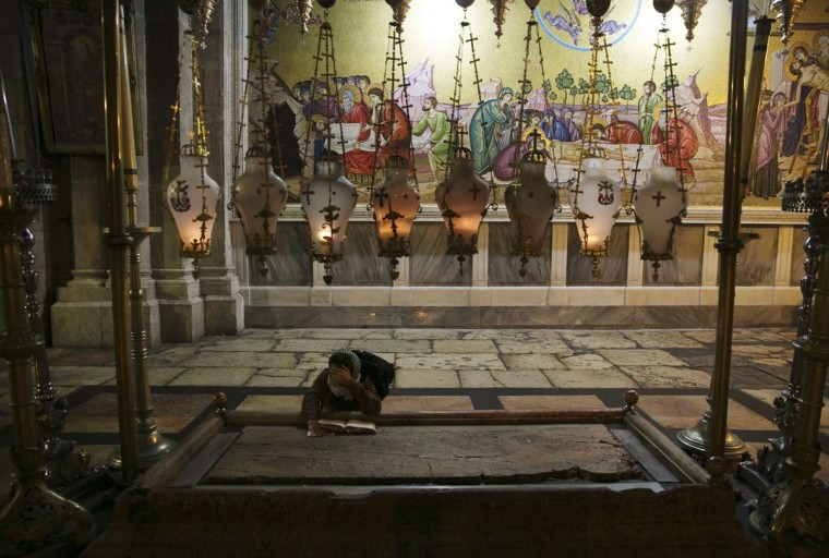 A Christian worshipper prays as she touches the Stone of the Anointing, where Christians believe the body of Jesus was prepared for burial, in the Church of the Holy Sepulchre, in Jerusalem's Old City, early morning August 25, 2013. (Darren Whiteside/Reuters)