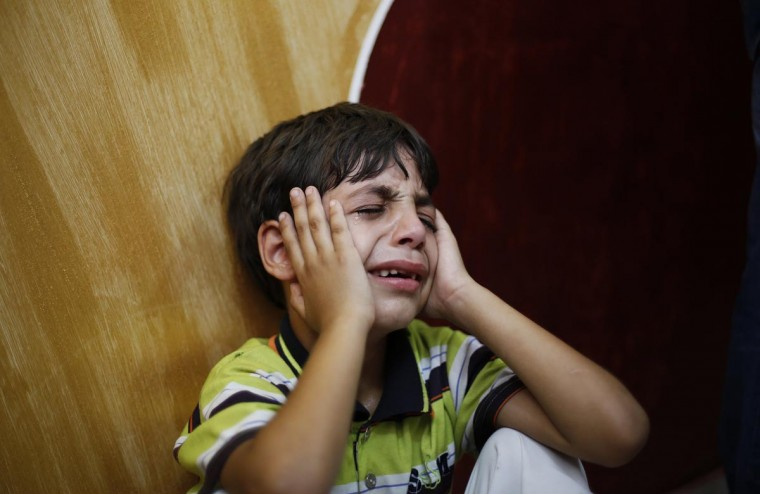 The son of Palestinian Huseen Awad mourns during his funeral in central Gaza Strip August 11, 2013. Israeli troops killed Awad who crossed in from the Hamas-ruled Gaza Strip on Saturday, fearing he was a security threat though he proved to be unarmed, military sources said. (Suhaib Salem/Reuters)