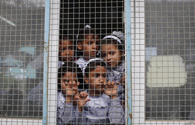 Palestinian schoolchildren look out the window of their classroom at a U.N.-run school in Dir al-Balah in the central Gaza Strip, on the first day of the school year, August 25, 2013. (Ibraheem Abu Mustafa/Reuters)