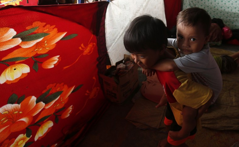A boy carries his brother on his back inside a makeshift tent at an evacuation centre for flood victims in Calumpit, Bulacan, north of Manila. The southwest monsoon that wreaked havoc on Metro Manila and nearby areas earlier this week is likely to weaken now that Typhoon Trami made landfall over China. (Erik De Castro/Reuters photo)