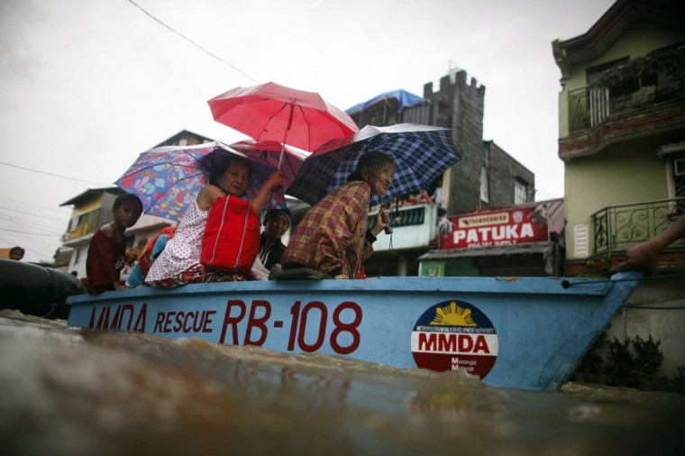 Residents ride in a rescue boat after being evacuated due to heavy flooding in Marikina, Metro Manila August 20, 2013. Monsoon rains reinforced by a tropical storm flooded half the Philippine capital in just 24 hours, triggering landslides and killing at least seven people, officials said on Tuesday. (John Javellana /Reuters)