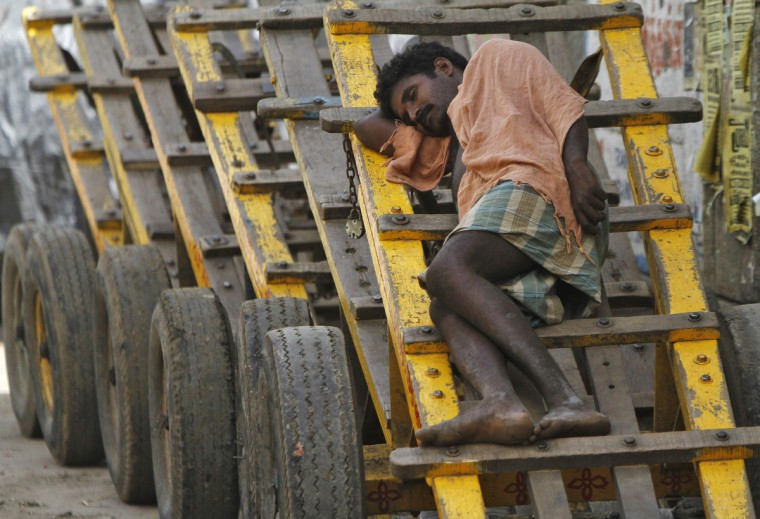A laborer takes a nap on a wooden cart at a wholesale vegetable market in the southern Indian city of Chenna. (Babu/Reuters photo)