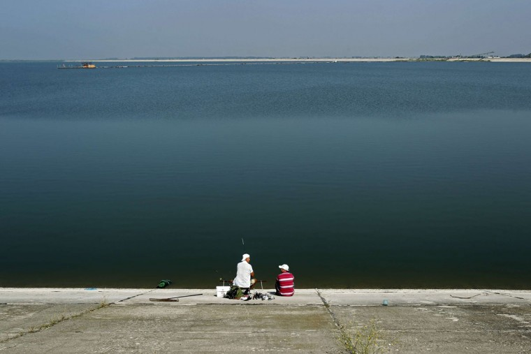 People enjoy fishing on a lake near Bucharest as temperatures reached 39 degrees Celsius (102 degrees Fahrenheit) in southern Romania, August 9, 2013. (Bogdan Cristel/Reuters)