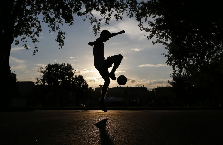 A youth practices his soccer skills as the sun sets at Gorky Park in Moscow. (Phil Noble/Reuters)