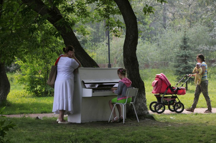 """A girl plays piano in the park in Russia's Siberian city of Krasnoyarsk. A group of young enthusiasts bought an old Soviet-made piano, adjusted it, painted white and placed in a park for free use by all visitors. The instrument is covered with a plastic foil at night and during rains. This is the group's first step in their project """"Free city entertainments"""", local media said. (Ilya Naymushin/Reuters)"""