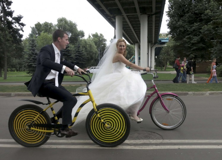 Boris Babkini (L) and his wife Yelena ride through Gorky Park on bicycles after having been married earlier in the day in Moscow, Russia. (Gary Hershorn/Reuters photo)