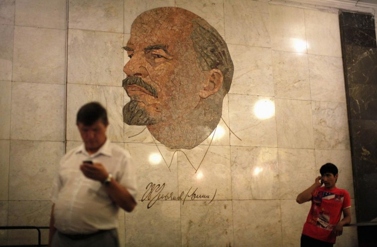 Men use their mobile phones as they stand in front of a mosaic depicting former Soviet leader Vladimir Lenin at Biblioteka Imeni Lenina metro station in Moscow August 13, 2013. (Lucy Nicholson/Reuters)