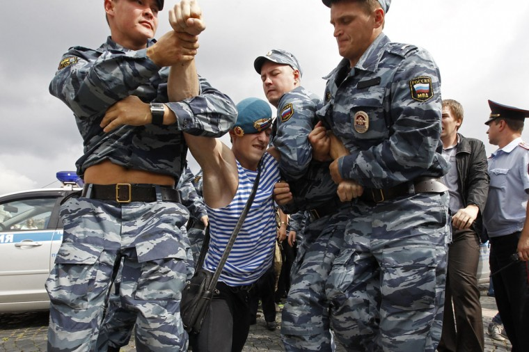 Police detain a former Russian paratrooper after he attacked an LGBT rights activist who was holding a one-man protest in St. Petersburg, August 2, 2013. Former servicemen were gathered in central St. Petersburg to celebrate Russian Paratroopers Day, an annual holiday for the Russian airborne troops celebrated since the Soviet era days. (Alexander Demianchuk/Reuters)