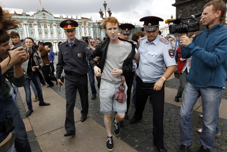 Police detain gay rights activist Kirill Kalugin after he was attacked by former Russian paratroopers during his one-man protest in St. Petersburg, August 2, 2013. Former servicemen were gathered in central St. Petersburg to celebrate Russian Paratroopers Day, an annual holiday for the Russian airborne troops celebrated since the Soviet era days. (Alexander Demianchuk/Reuters)