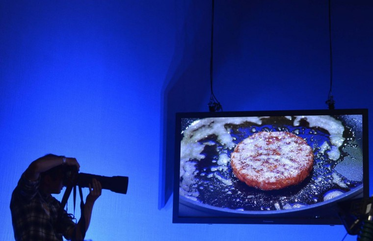 A photographer shoots in a television studio with a live screen view behind as the world's first lab-grown beef burger is cooked during a launch event in west London, August 5, 2013. (Toby Melville/Reuters)