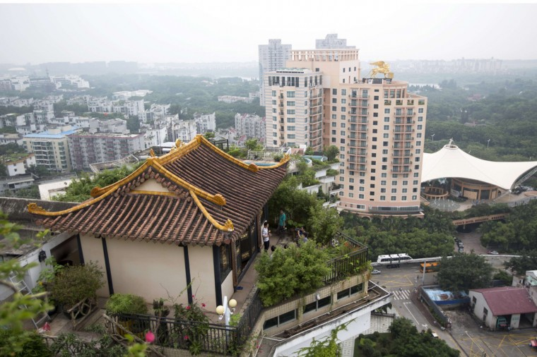 A privately-built illegal temple-like structure is seen on the top of a 20 story residential block in the southern Chinese city of Shenzhen. A police spokesman said that the elaborate temple-like structure is built illegally on the roof. The temple on top of the building in Shenzhen's Nanshan district is believed to have been there for at least three years, local media reported. The temple and the inaccessible rooftop had caused concerns over safety issues among some residents. But despite complaints from neighbors, the temple only came into the spotlight after a wealthy physician in Beijing was given 15 days to tear down his illegal villa and garden built atop a 26 story apartment block on August 12. (Tyrone Siu/Reuters photo)