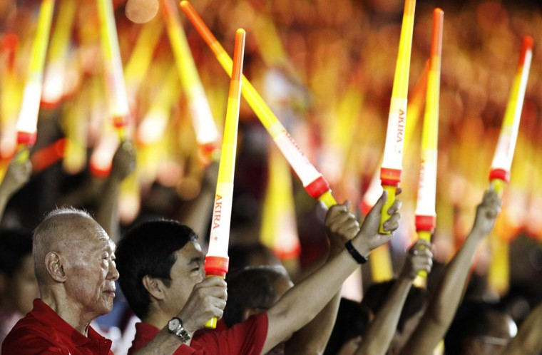 Former Prime Minister of Singapore Lee Kuan Yew (left) waves a light stick during Singapore's national day parade celebrations, August 9, 2013. The city state celebrates 48 years of independence on Friday. (Edgar Su/Reuters)