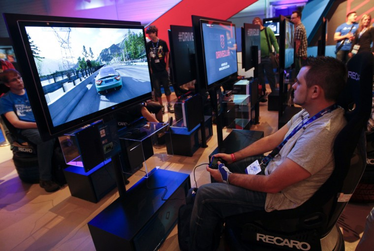 "Visitors play ""Driveclub"" with a Playstation 4 at the Sony exhibition stand during the Gamescom 2013 in Cologne August 21, 2013. Sony has had more than one million preorders worldwide for its new PlayStation 4 console. (Ina Fassbender/Reuters)"