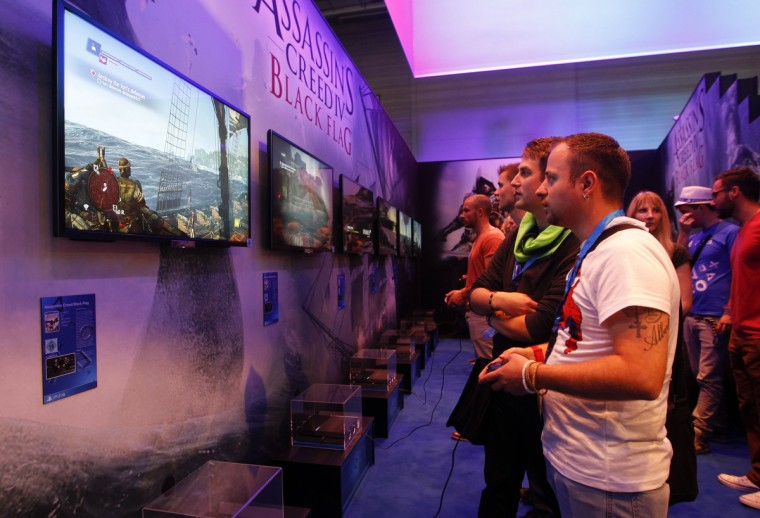 "Visitors play ""Assassins Creed IV Black Flag"" with Playstation 4 at the Sony exhibition stand during the Gamescom 2013 in Cologne. (Ina Fassbender/Reuters)"