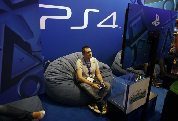 A visitor plays a Playstation 4 at the Sony exhibition stand during the Gamescom 2013 in Cologne, Germany. The Gamescom convention, Europe's largest video games trade fair, runs from August 22 to August 25. (Ina Fassbender/Reuters)