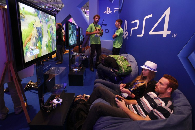Visitors play a Playstation 4 at the Sony exhibition stand during the Gamescom 2013 in Cologne. (Ina Fassbender/Reuters)