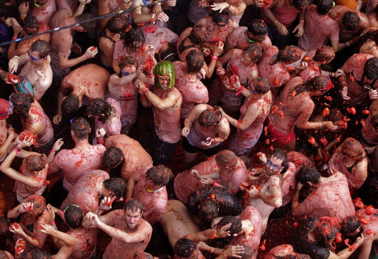 "Revelers battle with tomatoes during the annual ""Tomatina"" (tomato fight) in the Mediterranean village of Bunol, near Valencia. The origin of the tomato fight is disputed - everyone in Bunol seems to have a favourite story - but most agree it started around 1940, in the early years of General Francisco Franco's dictatorship. (Heino Kalis/Reuters)"