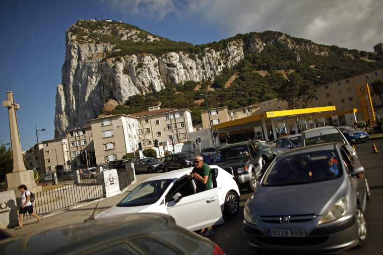 Drivers wait in line on a hot summer day to enter to Spain at its border with the British territory of Gibraltar in front of the Rock (rear) in Gibraltar, south of Spain on August 9, 2013. Spanish Prime Minister Mariano Rajoy on Friday threatened unilateral measures in a spat with Gibraltar over fisheries although he also said he hoped for talks soon with Britain about the disputed territory. (Jon Nazca/Reuters)